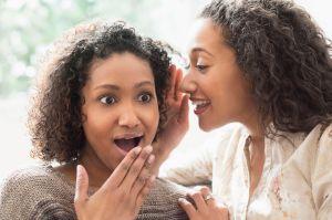 Surprised women whispering secrets