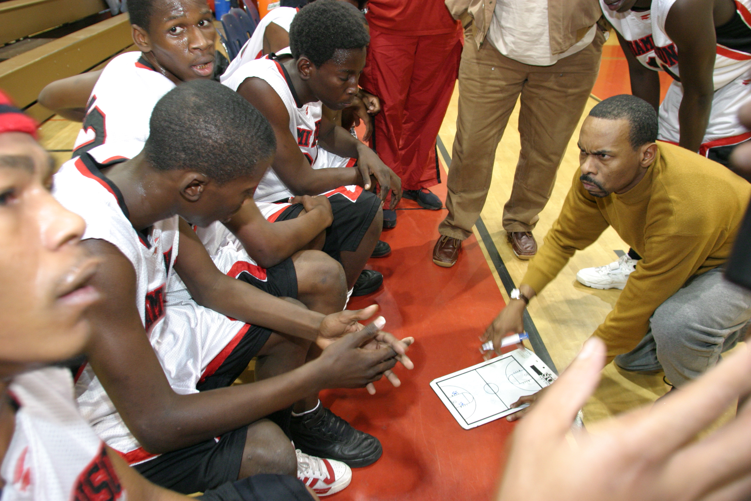 A coach talking to his students at the Edison High School vs. Miami High School basketball game.