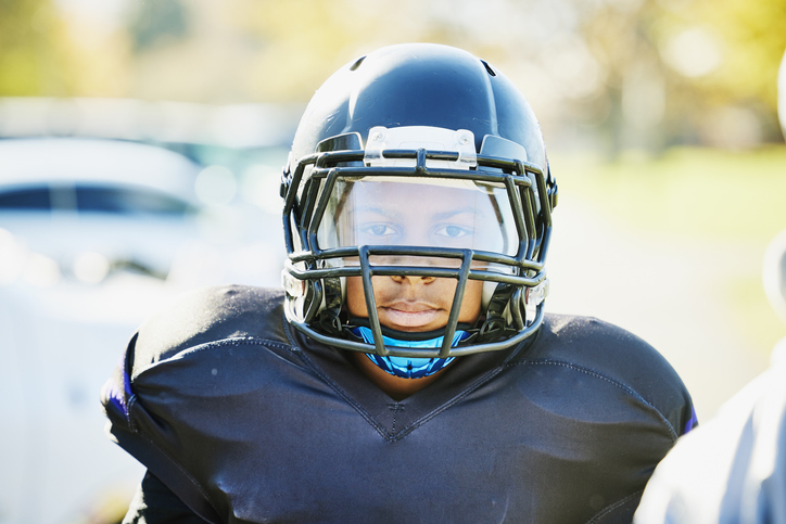 Medium shot portrait of boy in football gear before game on fall afternoon
