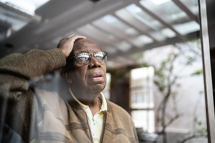 Worried senior man looking through the window at home